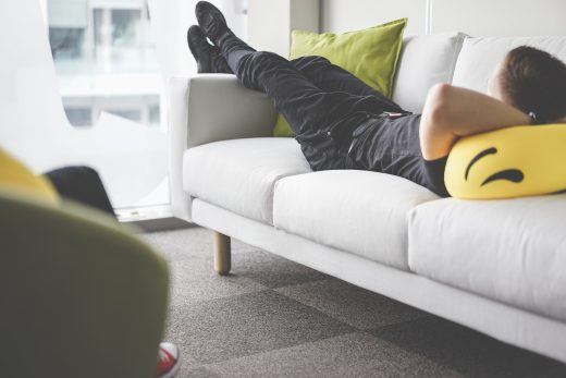 young-man-napping-on-white-sofa-in-the-office-picjumbo-com